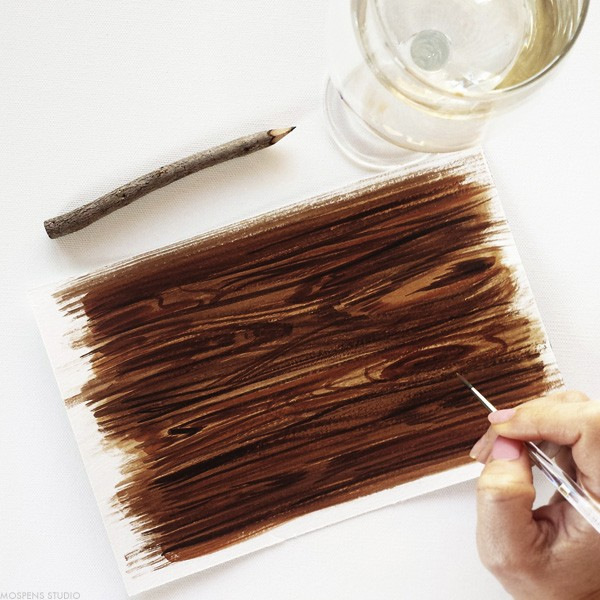 Artist hand-painting dark wood for a rustic wedding stationery suite | www.mospensstudio.com